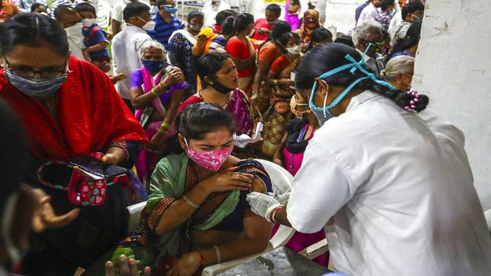 A health worker administers a dose of Covaxin as hundreds