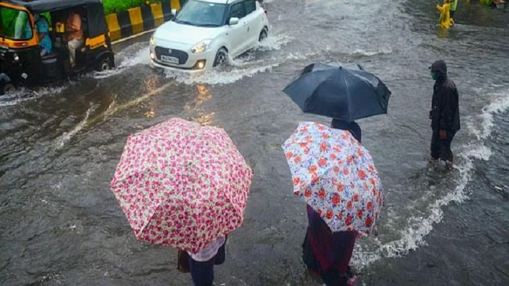 Commuters wait to cross a waterlogged street as vehicles