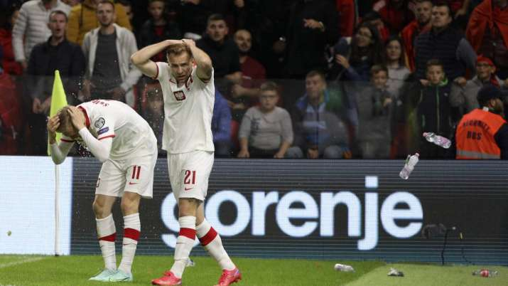 Poland's Karol Swiderski (left) holds his head as fans threw items shortly after scoring the opening