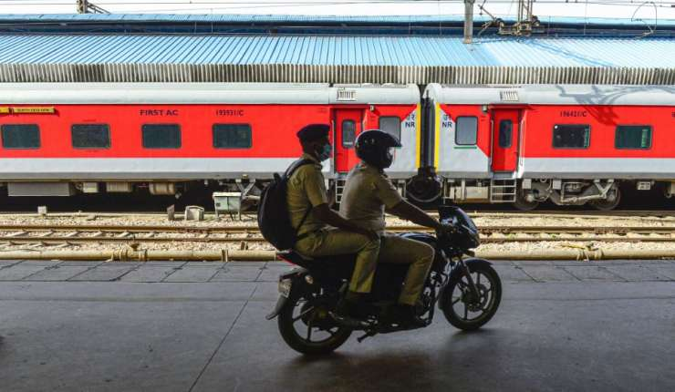 Policemen patrol on a bike along a stationed train during the nationwide lockdown, in wake of corona - India Tv